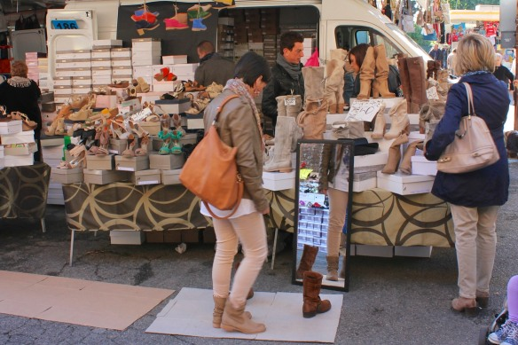 Pieces of cardboard are laid out in front of the shoe vendor's stall for trying on