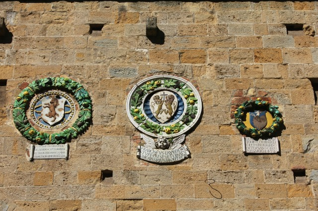 Emblems of the hated Florentine rulers on the façade of Palazzo dei Priori.