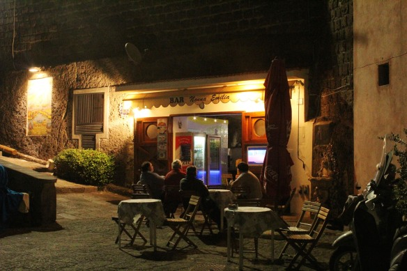 After dinner, locals watch la partita di calcio  (soccer game) at an outdoor TV.