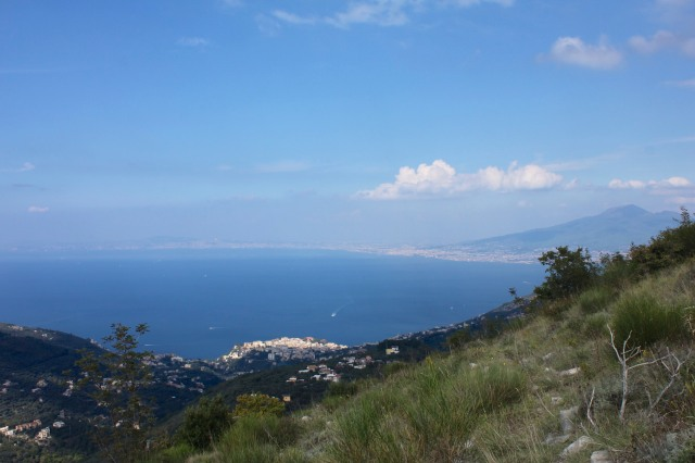 Vico Equense is momentarily lit up by sunlight.  To the right on the far shore Vesuvius looms over Naples.